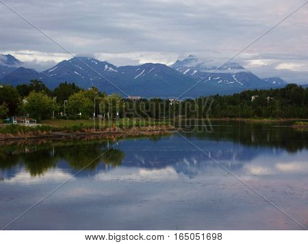 landscape view of snow capped mountains reflecting on the water. Spring or summer day in Anchorage Alaska. Calm peaceful trip to the lake
