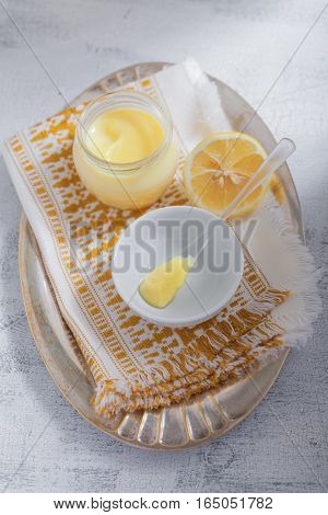 Lemon kurd with a spoon served on a table.