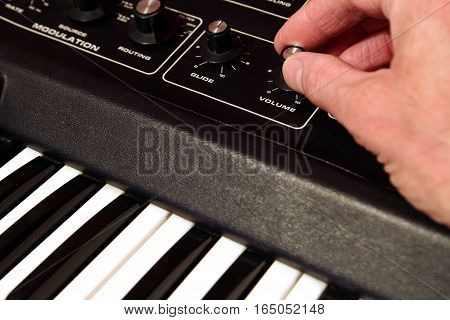 Man's Hand Adjusting The Volume On A Vintage Analog Synth