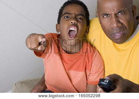 Father and son yelling at their television.