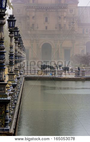 Rainy day in Spanish Square or Plaza de Espana in Sevilla, Spain. Vanishing point leading to a quiet horse and carruage.