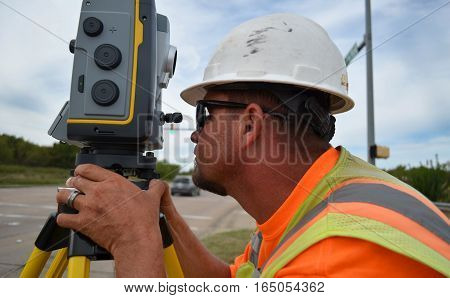 Man In Safety Gear Surveying A Road