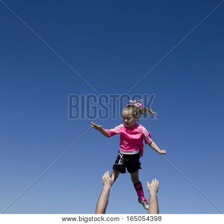 Young girl in soccer uniform being thrown into the air.