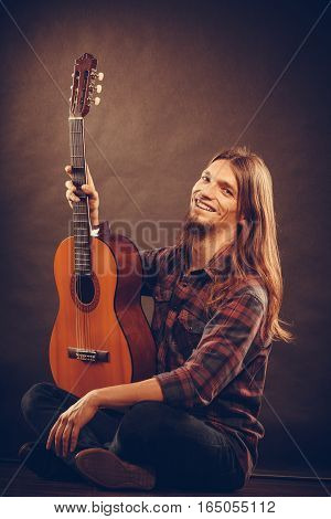 Music hobby concept. Hanppy artist with wooden guitar. Young man is sitting on the floor and holding the instrument.