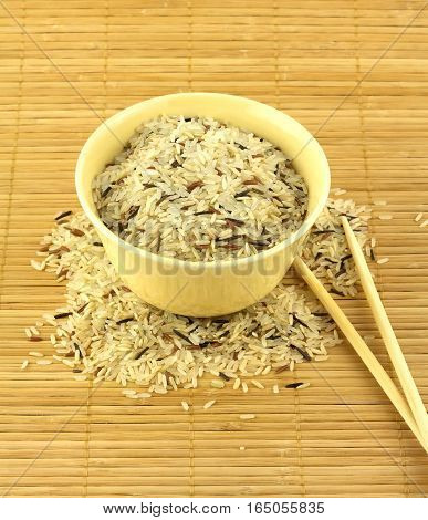 China color rice in yellow bowl and chopsticks on brown straw mat closeup vertical photo