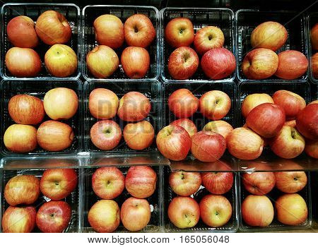 Full frame rows of red apples grouped and stacked on display shelves for sale