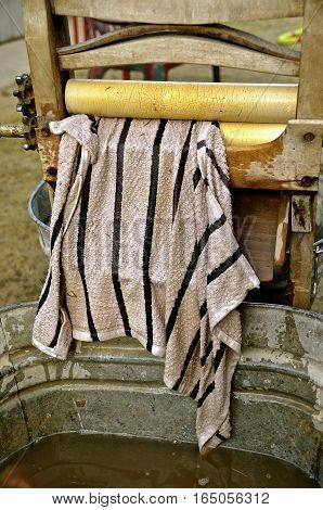 A wet towel emerges from the vintage wringer washing machine heading to the tub of water below.