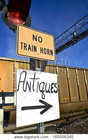 Signs indicates the passing locomotive and train passing through an intersection will not sound off it's horn and antiques available to the right.