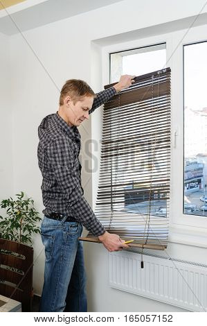 Installing wooden blinds. A man holds the unfolded jalousie.