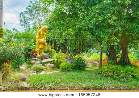 Landscape design of relax tropical garden with statue of a woman with watering can