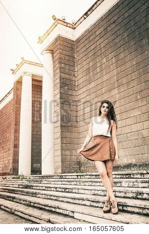 Beautiful girl with long curly hair and skirt. Outdoors in the old city. A beautiful young woman is outdoor with antique marble columns. White shirt with no sleeves and brown skirt. Lean and healthy body. Left copyspace.