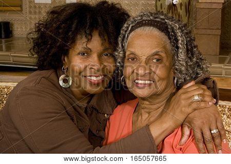 Mature African American mother hugging her daughter.
