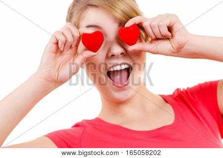 Smiling funny playful girl holding red hearts over eyes. Valentines day love happiness concept.