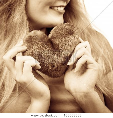 Woman blonde long hair girl holding heart love symbol studio shot isolated on white. Valentines day happiness concept