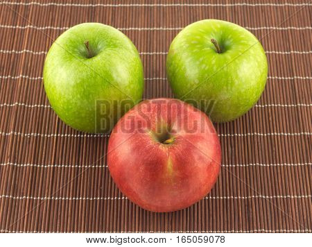Three color ripe apples on brown wicker straw mat close up