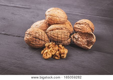 Walnut kernels and whole walnuts on old wooden table