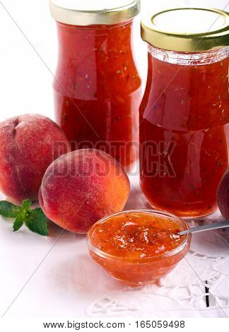 Peach and rosemary jam in small bowl and jars selective focus