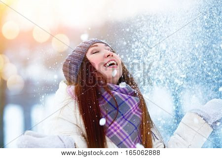 Winter young woman portrait. Beauty Joyful Model Girl raising hands, spinning and laughing, having fun in winter park. Beautiful young woman laughing outdoors. Enjoying nature, wintertime.