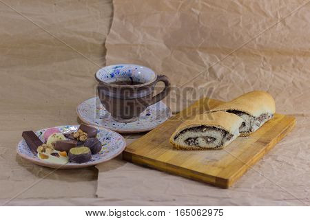 cup of tea and a roll with poppy seeds on a crumpled paper. tea and roll with poppy seeds on the board. tea and pastries