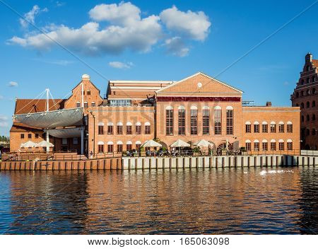 GDANSK, POLAND - SEPTEMBER 2, 2016: Baltic Philharmonic Hall on the Olowianka Island in Gdansk and Motlawa River at sunset light