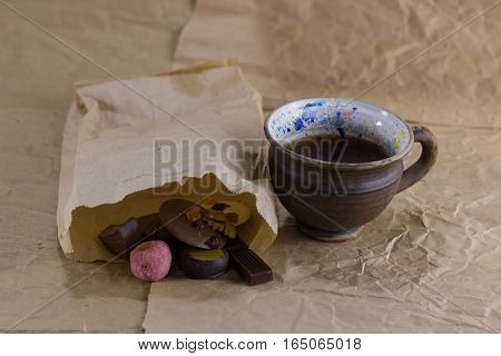 cup of tea near the paper bag with sweets on crumpled paper. tea and sweets
