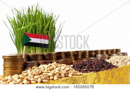 Sudan Flag Waving With Stack Of Money Coins And Piles Of Wheat And Rice Seeds