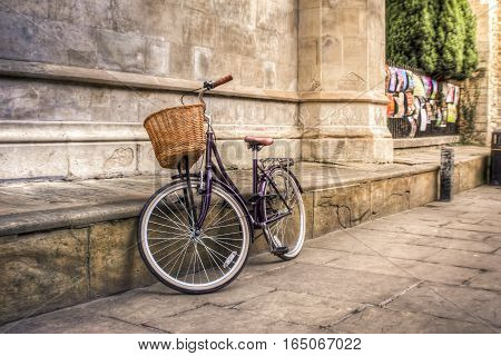 Purple vintage bicycle in an iconic old street