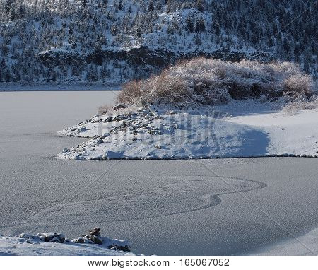 Fresh snow covers the banks and the ice on Ochoco Reservoir in Crook County in Central Oregon on a sunny winter day.
