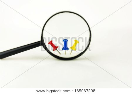 Three drawing pins of different color are visible through a magnifying glass