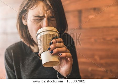 Young Woman Drinking A Coffee And Burning Her Tongue