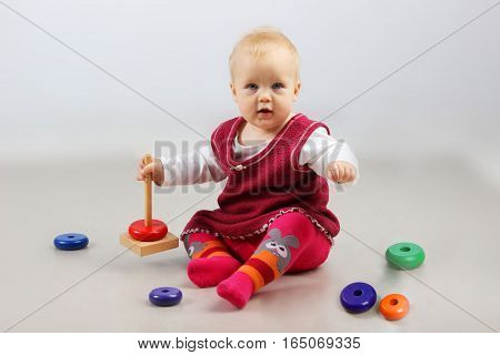 Shot of an adorable baby girl in red clothes playing with some toys.