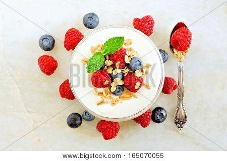 Yogurt With Sweet Berries And Granola, Overhead Scene On White Marble