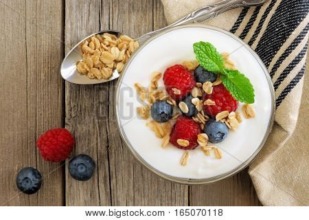 Greek Yogurt With Raspberries, Blueberries And Granola, Overhead Scene On Rustic Wood