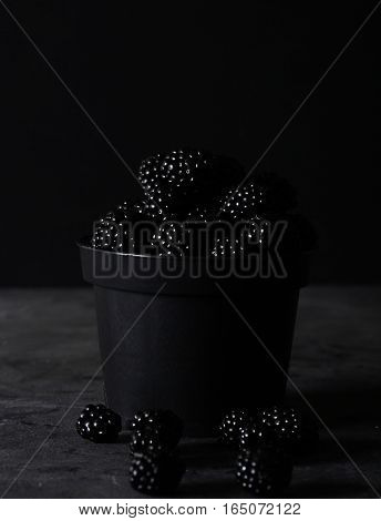 Blackberry. Blackberries in black decorative vase on a dark abstract background. Copyspace. Healthy food concept. Colorful festive still life. Fresh berries. Art food photography. Dark light