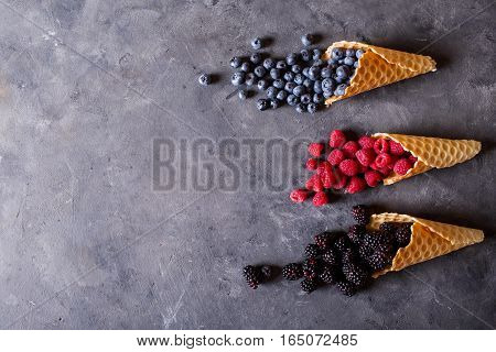 Waffle with fresh berries. Berries. Raspberries blackberries blueberries in waffle cones on a gray abstract background. Copyspace. Healthy food concept