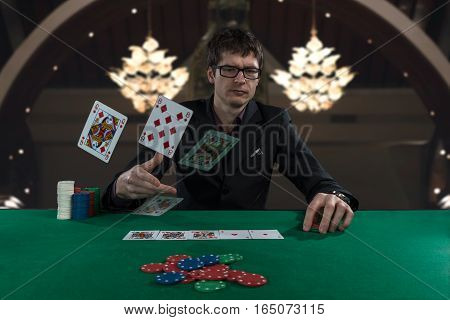 angry poker player in suit throwing cards