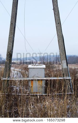 old damaged electrical pole on wilderness at the cold winter morning
