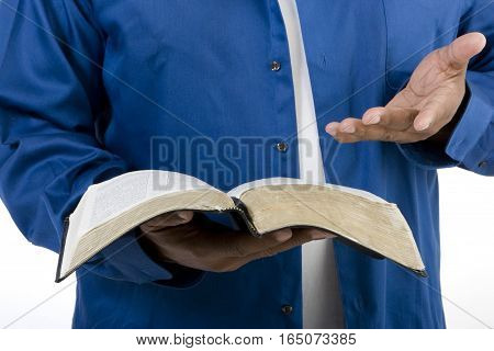 Unrecognizable man reading the Bible isolated on white.