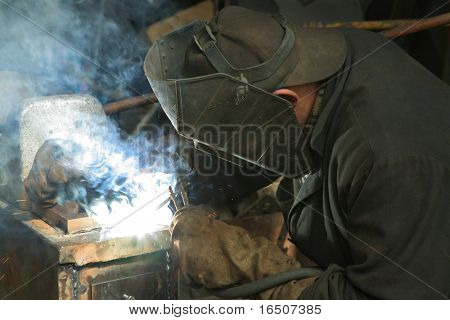 The worker is engaged in welding on a metal works