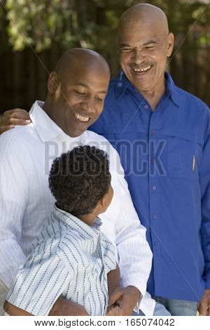 Grandfather with his adult son and grandchild at the park.