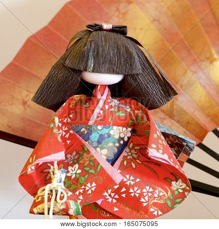 A Japanese doll with a fan in brown and gold background.