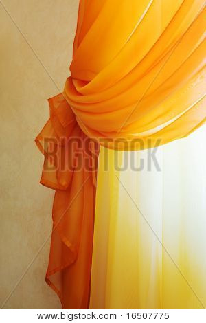 Beautiful translucent orange curtains in an apartment