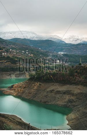 Landscape with green Dim Cay storage pond and mountain range covered with snow on winter day in Alanya, Southern Turkey