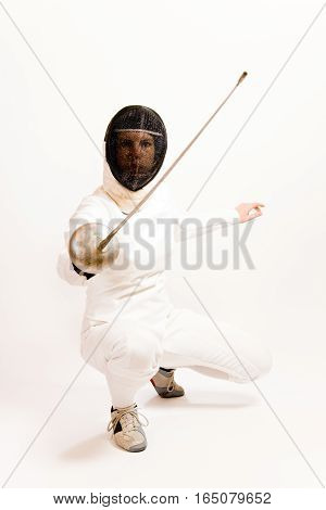 woman dressed in a fencing suit and mask, kneeling and holding up her rapier