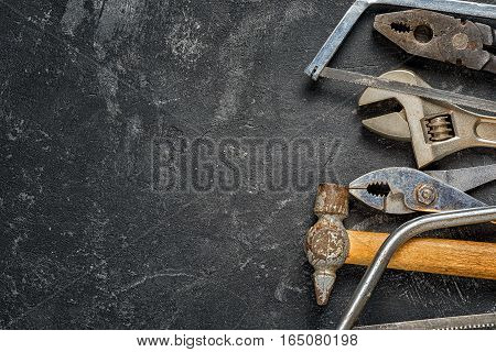 Tools: hammer wrench pliers hacksaw on the black grungy cement background with copy space for your text. Home diy concept.