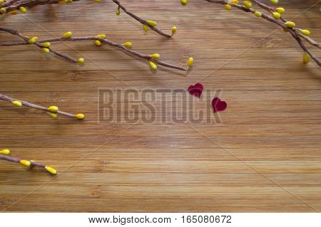 small red hearts on bamboo board with branch of yellow artificial flowers