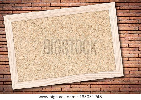 Cork board or Empty bulletin board with a wooden frame on brick wall background with copy space for text or image.