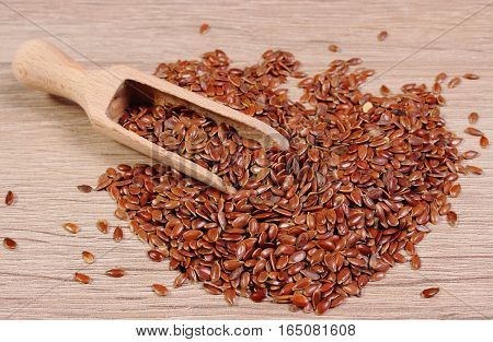 Heap Of Linseed With Spoon On Wooden Background
