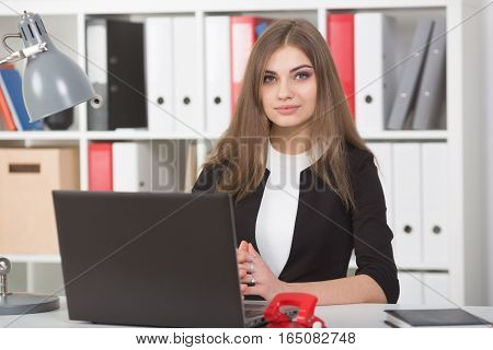 Businesswoman sitting at a desk in the office right shoulder forward. Hands on the table.