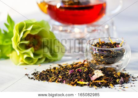 Dry leaves of french earl grey flowered tea with teapot and green flower on the background on the white table